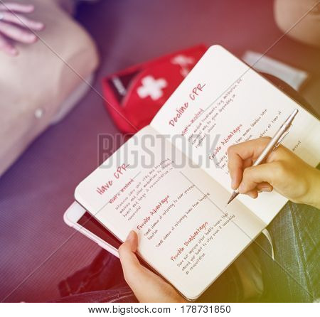 Hand writing the CPR detail on the book