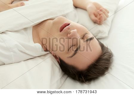 Tired young man sleeping in bed at home