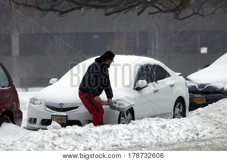 BRONX NEW YORK - MARCH 14: Man digs out car with shovel during snow storm. Taken March 14 2017 in New York.