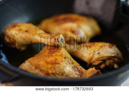 Appetizing fried chicken legs on a black frying pan