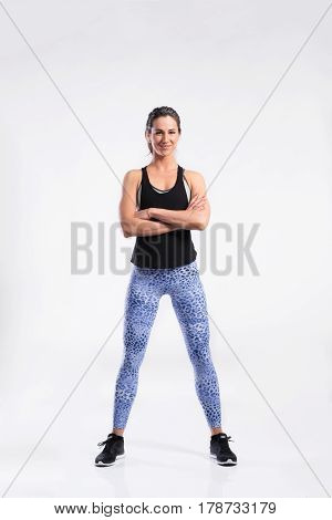 Attractive young fitness woman in black tank top and blue sports leggings, arms crossed. Slim waist, perfect fit female body. Studio shot on gray background.
