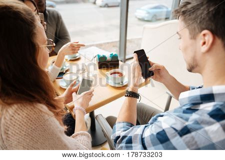 Top view of youngsters using their smartphones while sitting at cafe during lunch break.