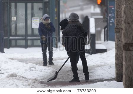 BRONX NEW YORK - MARCH 14: Man shovels snow during snow storm. Taken March 14 2017 in New York.