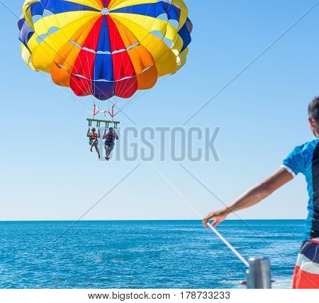 Happy couple Parasailing in Dominicana beach in summer. Couple under parachute hanging mid air. Having fun. Tropical Paradise. Positive human emotions feelings joy.