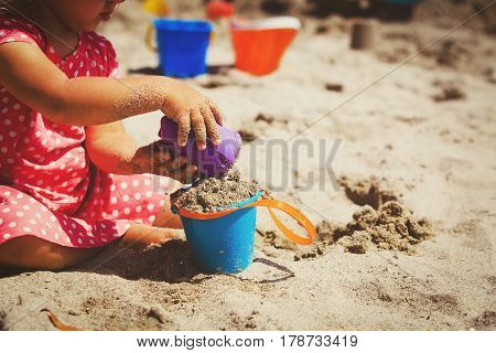 hands of little girl play with sand and toys on beach