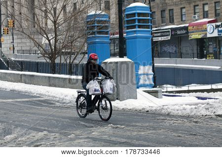 BRONX NEW YORK - MARCH 14: Man doing delivery on bike during snow storm. Taken March 14 2017 in New York.