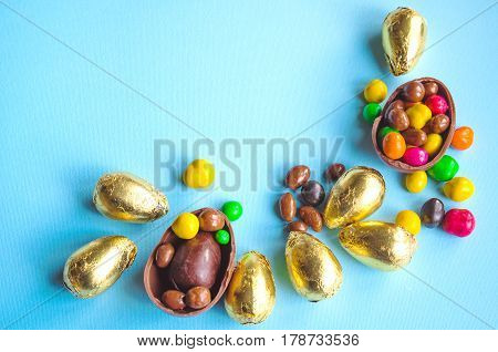White Easter Bunny With Chocolate Eggs Wrapped In Golden Foil And Candies On Light Blue Background