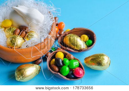White Easter Bunny In A Decorative Nest With Chocolate Eggs Wrapped In Golden Foil