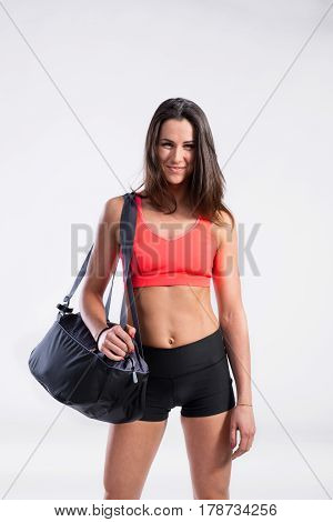 Attractive young fitness woman in orange sports bra and black shorts, carrying sports bag. Slim waist, perfect fit female body. Studio shot on gray background.