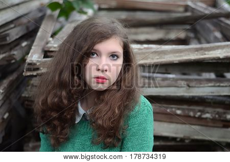 Young girl with long brown hair and blue eyes wearing a green sweater in the garden in the summer