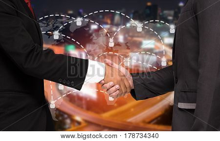 Double exposure of businessman handshake with world map social media network connection, successful business meeting on blurred night city background, color tone effect.