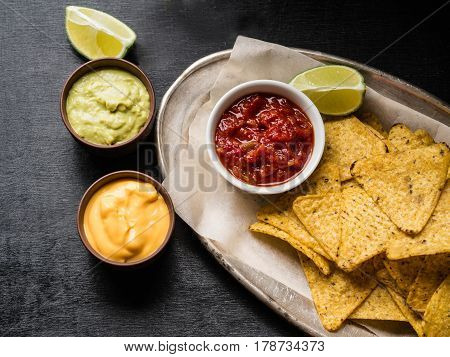 Mexican nachos chips  with salsa sauce, cheese sauce and guacamole sauce and lime slice