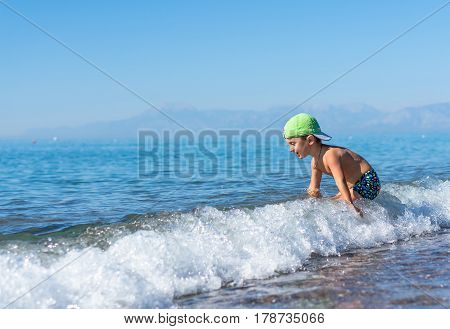 Smiling little baby boy in green baseball cap playing in the sea. Positive human emotions feelings joy.