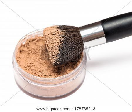 Close up of make-up brush with jar of loose cosmetic powder on white background. Shallow depth of field, focus on powdery brush bristle