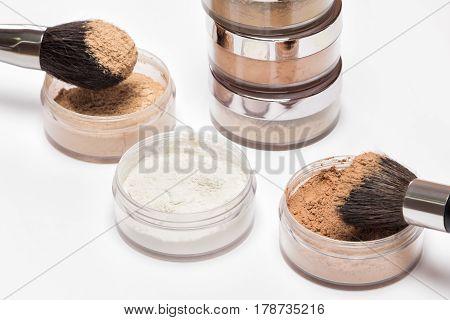 Jars of loose cosmetic powder different colors and shades with makeup brushes on light background. Selective focus on content of nearest jars