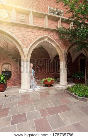 Beautiful young woman stands leaning on a column in an arched passage of the ancient university building in Krakow. Poland. Studying abroad. Student life. The ancient universities of Europe