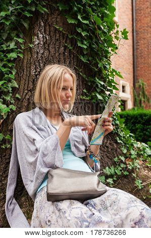 Beautiful young woman sitting leaning on a tree in the middle of ivy on a background of the ancient university building in Krakow and studies city map . Poland. Studying abroad. Student life. The ancient universities of Europe
