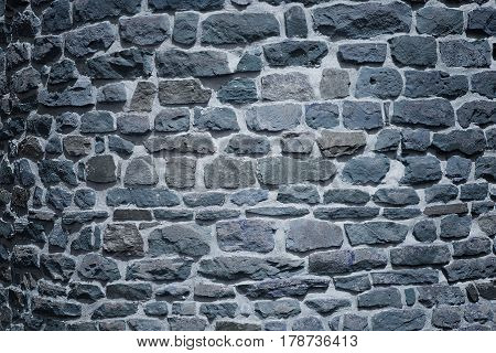 old castle wall background with irregular stone blocks at night