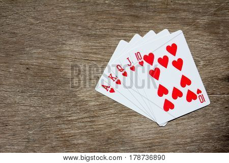 Five card of red heart royal straight flush on wooden background