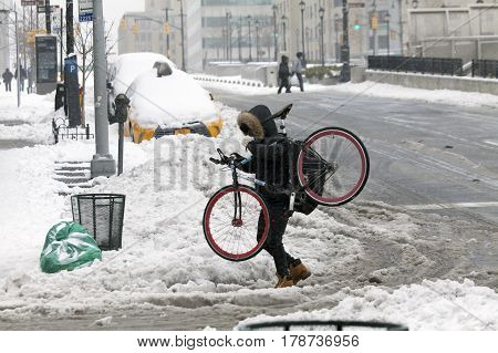 BRONX NEW YORK - MARCH 14: Man carries bike while crossing street in snow storm. Taken March 14 2017 in New York.