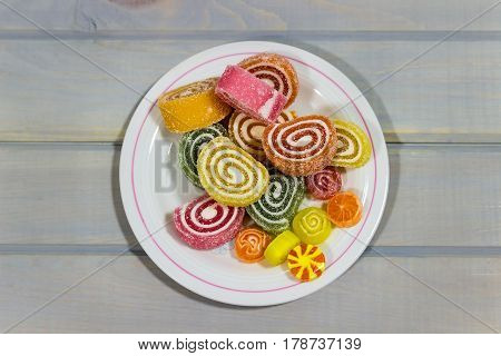 Fruit jelly on a wooden table. Bright candy on a gray background. View from above.