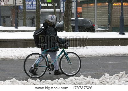 BRONX NEW YORK - MARCH 14: Man walks with bike during snow storm. Taken March 14 2017 in New York.