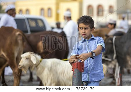 Nizwa Oma 24th March 2017: omani boy at a goat market