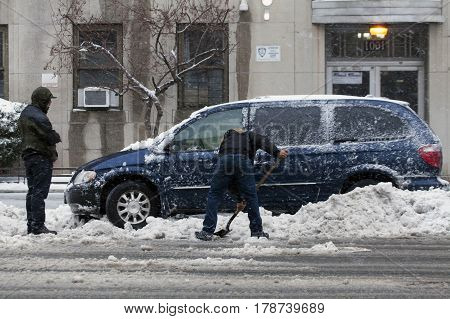 BRONX NEW YORK - MARCH 14: Man shovels to free car from snow. Taken March 14 2017 in New York.