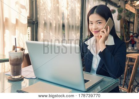Smiling young asian executive business woman using her cell phone and working on her computer indoor golden hour lighting coming through the large windows vintage retro style look
