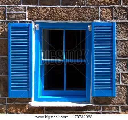 Blue window with shutters in late afternoon