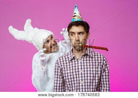 Rabbit frightening drunk man over purple background. Birthday party. Copy space.