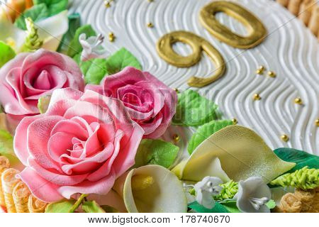 Delicious cake with roses lily leaves and figures 90 Years on light blue wooden table close up with selective focus.