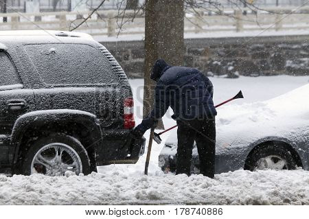 BRONX NEW YORK - MARCH 14: Man cleans car with brush during snow storm. Taken March 14 2017 in New York.