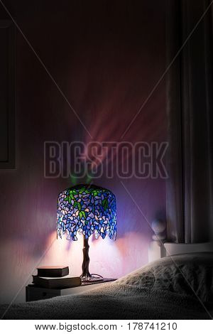 Light reflections in a pretty pink bedroom at night from a Tiffany style lamp. Deep shadows and glowing coloured light from the wisteria design stained glass creates a cosy mood. Copy space.