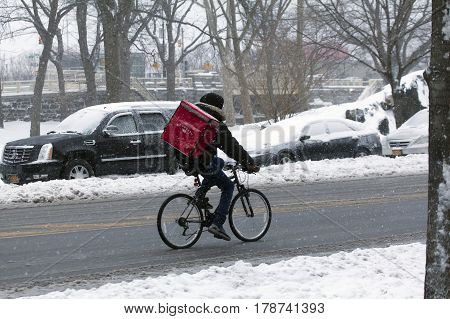 BRONX NEW YORK - MARCH 14: Person making delivery on bike during snow storm. Taken March 14 2017 in New York.