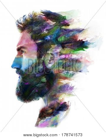 Profile portrait of a young, attractive, bearded man combined with colourful watercolour painting dissolving