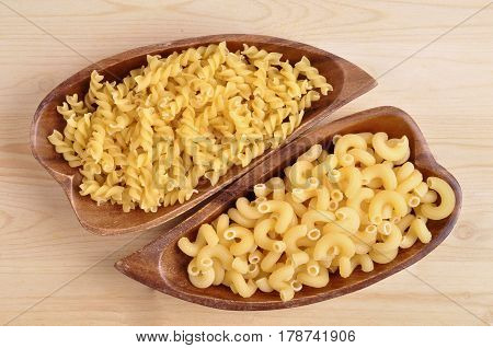 Raw pasta in a wooden bowl close-up on a wooden table