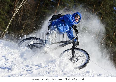 Cyclist on mountain bicycle, extreme cycling in flying snow near winter forest, sunny cold day