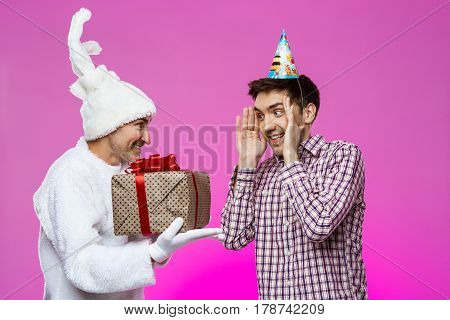Rabbit giving birthday gift to drunk man over purple background. Copy space.