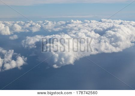 Thick Fluffy White Clouds On Blue Sky Over Idyllic Sea