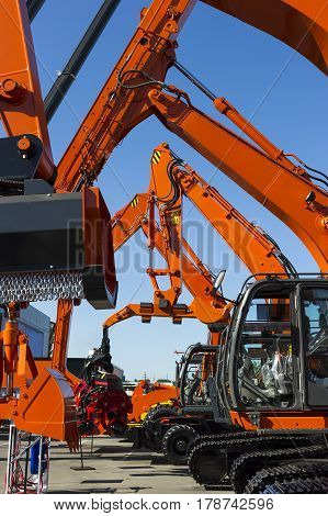 Bulldozer, excavator, tractor, front end loader and other orange construction machines with scoop, shovel, jackhammer and another equipment in row, heavy industry, blue on background