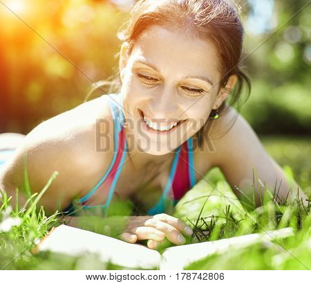 Beautiful girl lies on meadow and reads the book. Education and vacation concept