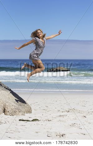 Blonde female in a dress is jumping off a rock at the beach
