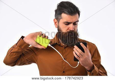 bearded man long beard brutal caucasian hipster with moustache charging mobile or cell phone with green power bank battery has serious face in brown color shirt isolated on white background