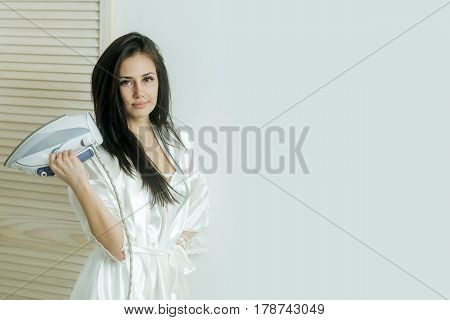 pretty girl or beautiful woman housewife with long brunette hair in sexy dressing gown with electric iron in hand indoors on white wall background. Housework and housekeeping copy space