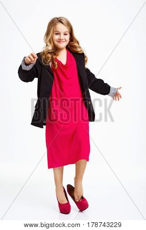 Funny girl in mother's jacket, fancy dress and pink heels shoes isolated on white background.
