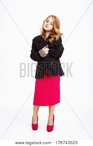 Curly bonde girl in beautiful pink dress, covering herself with black jacket, lookng straight