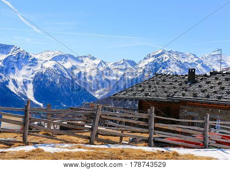 ULTIMO, ITALY - MARCH 20, 2017: The mountain restaurant Schwemmalm in the Ultental ski area with melted snow and green grass in front and snowy mountain panorama in the back.