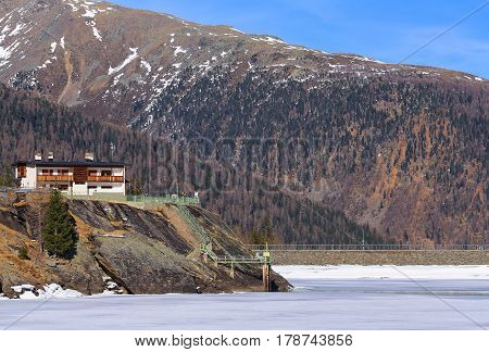 WEISSBRUNN, ITALY - MARCH 20, 2017: The reservoir Weissbrunnsee in the Ulten Valley in South Tyrol. The lake is part of the hydropower production in the valley.