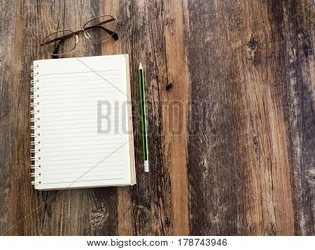 Pencils notebooks and glasses are placed on wooden boards on the left side.